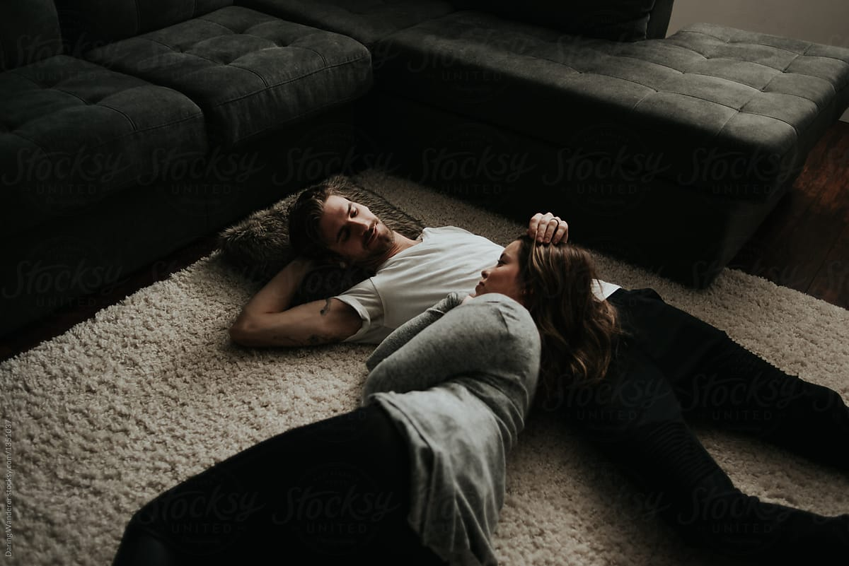 Young Couple Cuddling Lying On Living Room Floor Apartment by Jess Craven