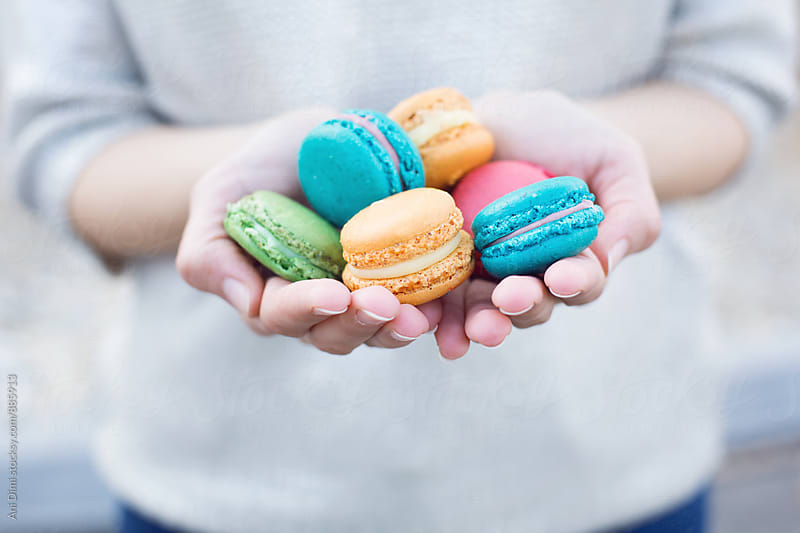 Holding a bunch of macaroons by Ani Dimi for Stocksy United