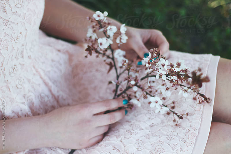 Young woman holding cherry blossom twig in her hands by Jovana Rikalo for Stocksy United