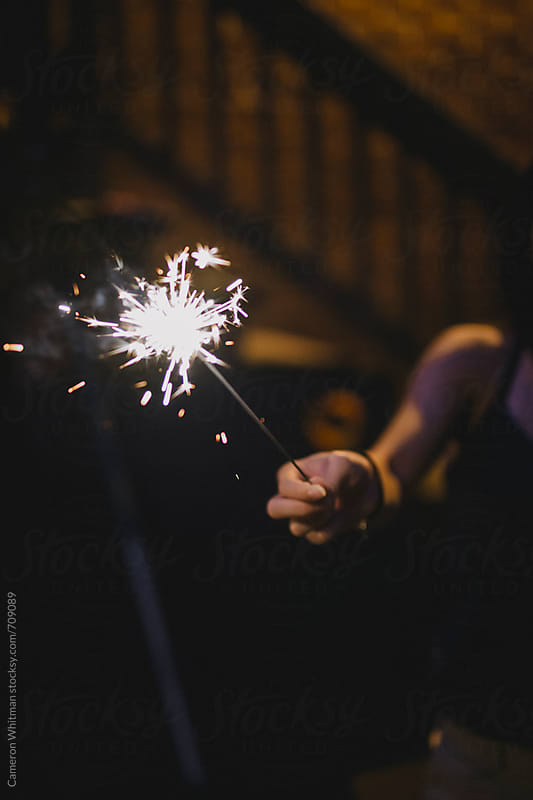 Hand holding sparklers  by Cameron Whitman for Stocksy United