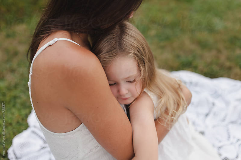 Close up of a mother and daughter cuddling outdoors by Amanda Worrall for Stocksy United