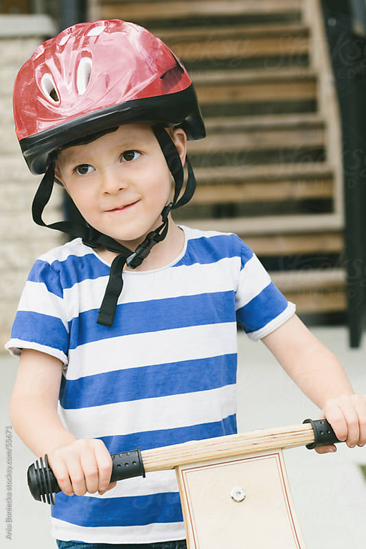 Boy wearing a red helmet on his bike by Ania Boniecka for Stocksy United