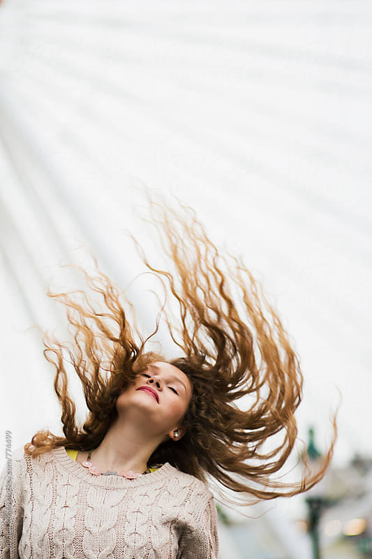 Young woman with her hair flying off to one side by Jovana Rikalo for Stocksy United