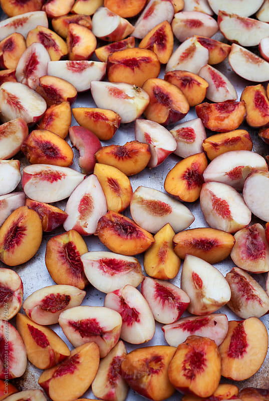 Huge tray of sliced, organic peaches by Carolyn Lagattuta for Stocksy United