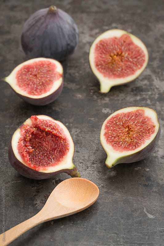Fresh figs on rustic board and a wooden spoon by Elisabeth Coelfen for Stocksy United
