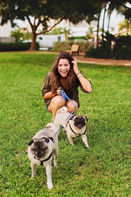 Girl playing with dogs by Ellie Baygulov for Stocksy United