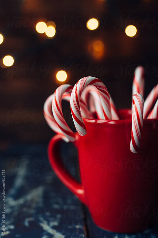 Candy canes in a red cup and Christmas lights by Gabriel (Gabi) Bucataru for Stocksy United