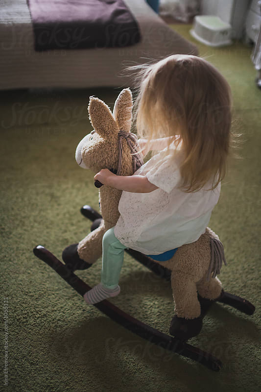 Little girl on a rocking horse by Irina Efremova for Stocksy United