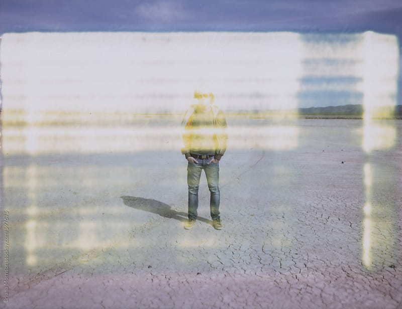 Man standing in a Dry lakebed with Light Leaks by Briana Morrison for Stocksy United