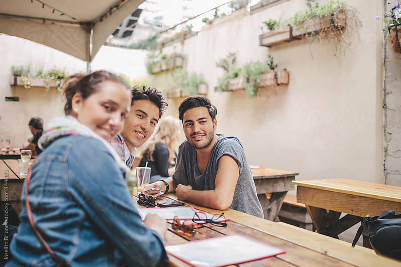 Group of Friends Hanging Out in a Cafe Restaurant by Joselito Briones for Stocksy United
