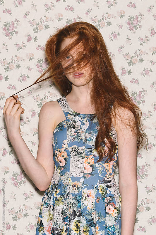 Young woman covering face with red hair by T-REX & Flower for Stocksy United
