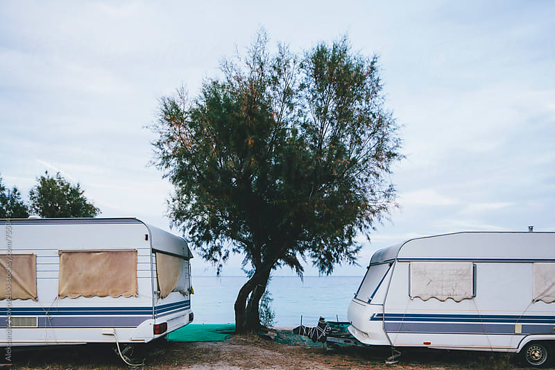 Two caravans and tree between them at the seaside, on a cloudy day by Aleksandar Novoselski for Stocksy United