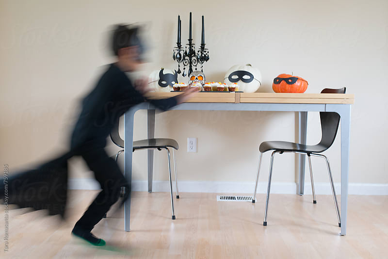 masked child sneaking up on Halloween party treats by Tara Romasanta for Stocksy United