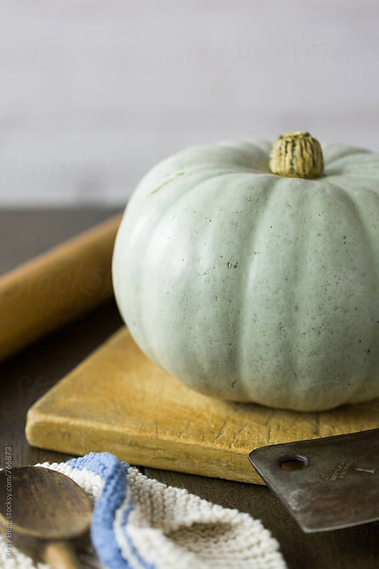 Whole Crown Prince pumpkin with a blue grey skin on kitchen table by Kirsty Begg for Stocksy United