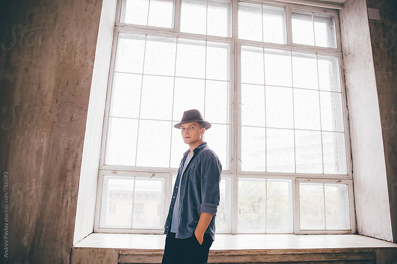 Man dressed in hat and denim shirt standing in front of window by Andrey Pavlov for Stocksy United