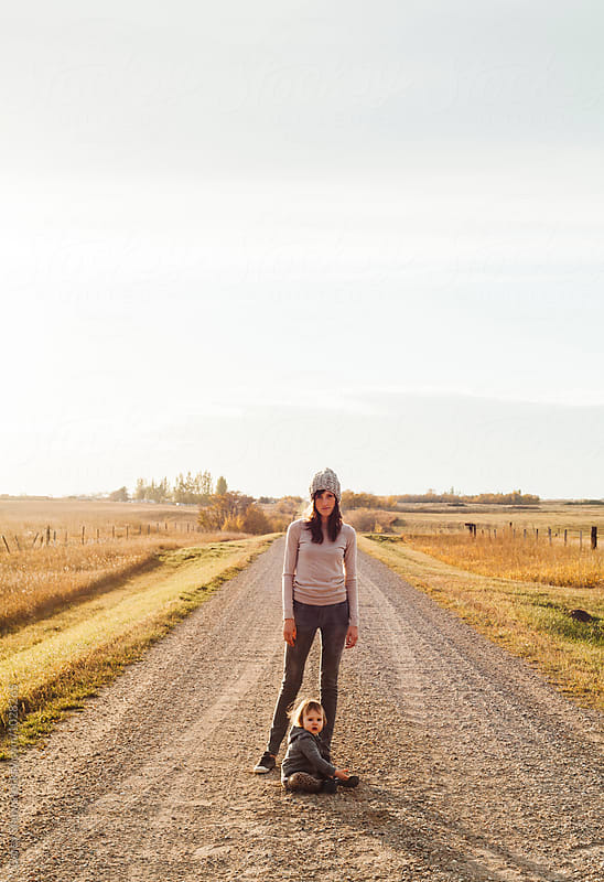 Mother and daughter on gravel road in the prairies  by Carey Shaw for Stocksy United