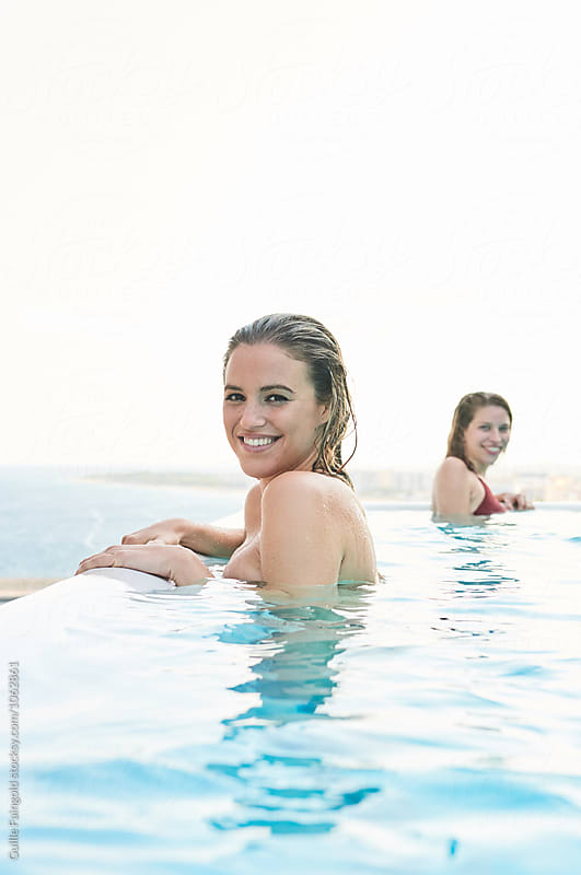 happy blonde in pool looking at camera with toothy smile by Guille Faingold for Stocksy United