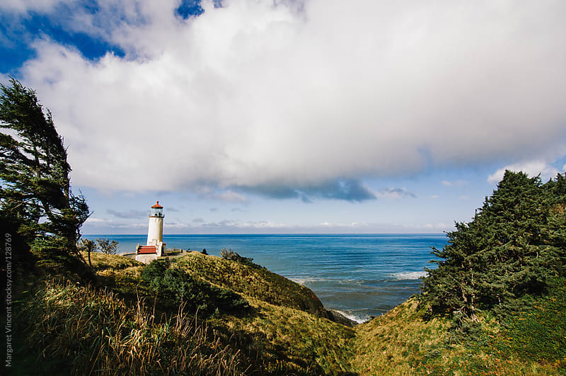 view of a lighthouse on a cliff above the ocean by Margaret Vincent for Stocksy United