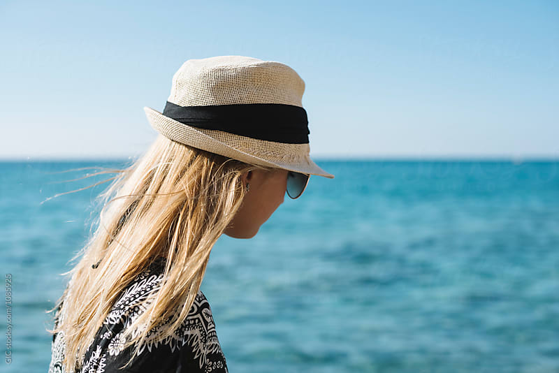 Young blonde woman with hat against sea by Simone Becchetti for Stocksy United