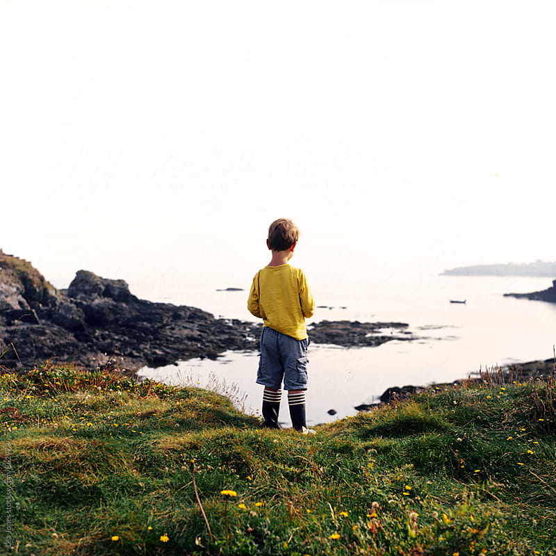 Little boy standing by the sea by Léa Jones for Stocksy United