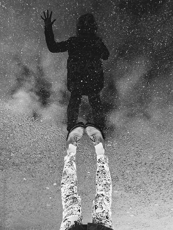 Girl waving while reflecting on asphalt puddle by Eric Bowley for Stocksy United
