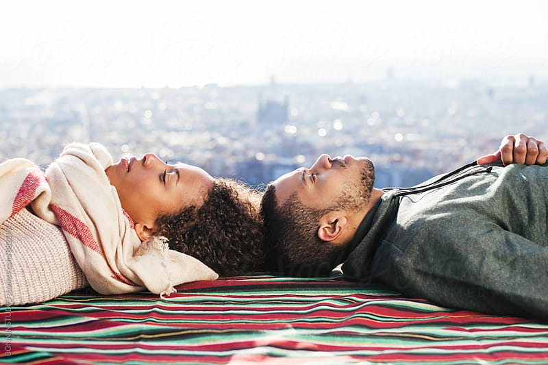 Mixed race couple resting on striped blanket above Barcelona. by BONNINSTUDIO for Stocksy United