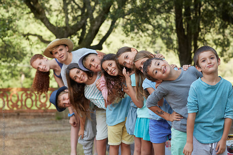 Group portrait of ten children at an outdoors party in a fun mood by Miquel Llonch for Stocksy United