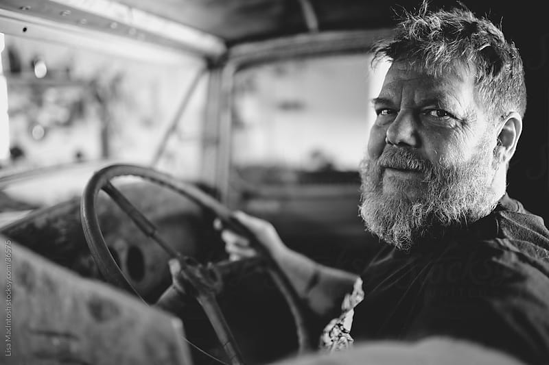 bearded tattooed man sitting inside vintage truck by Lisa MacIntosh for Stocksy United