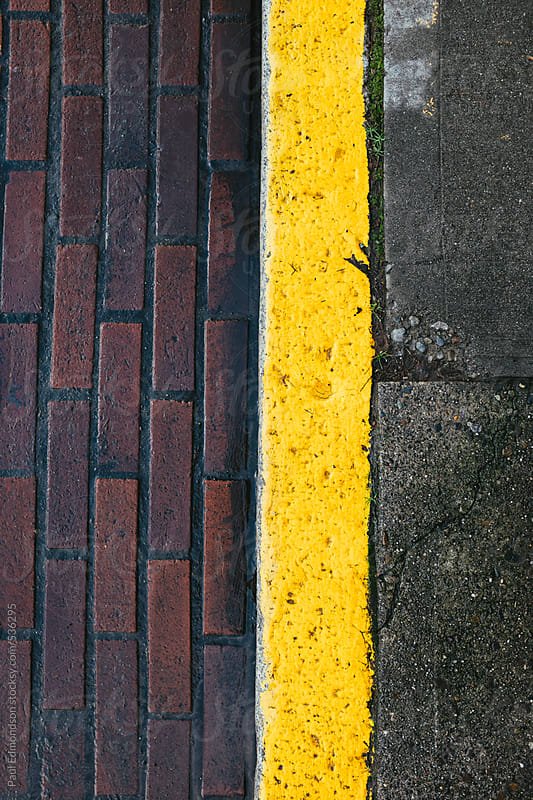 Painted yellow curb along brick sidewalk and street by Paul Edmondson for Stocksy United