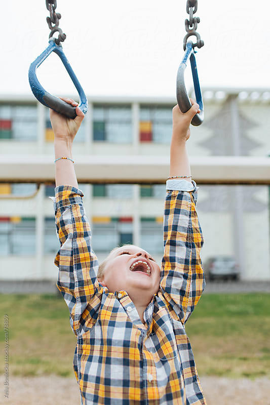 Laughing boy holding onto rings at a school playground by Ania Boniecka for Stocksy United