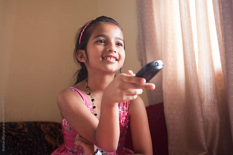 A young girl watching tv. by Shikhar Bhattarai for Stocksy United