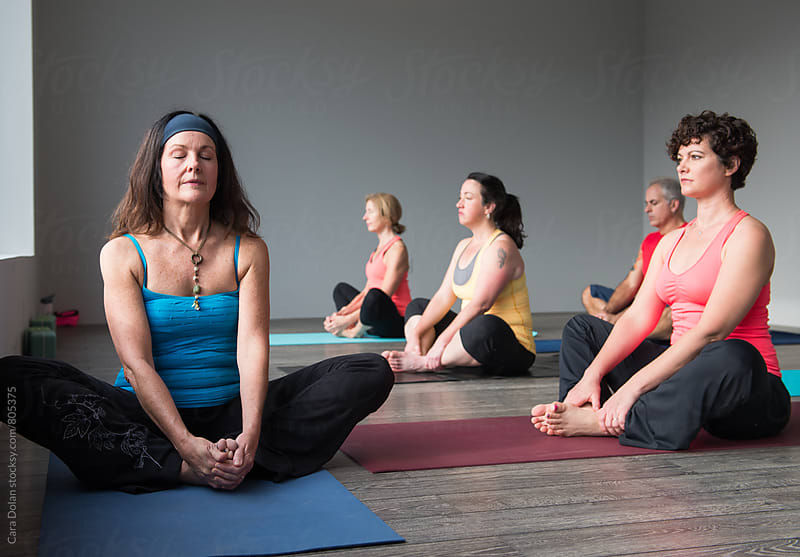 Yoga instructor teaches class in modern studio by Cara Slifka for Stocksy United
