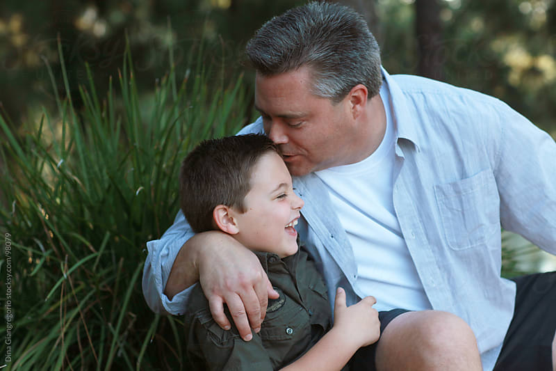 Young boy laughing as his father kisses him by Dina Giangregorio for Stocksy United