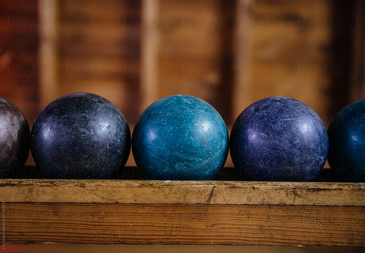 Well-used candlepin bowling balls lined up in a bowling