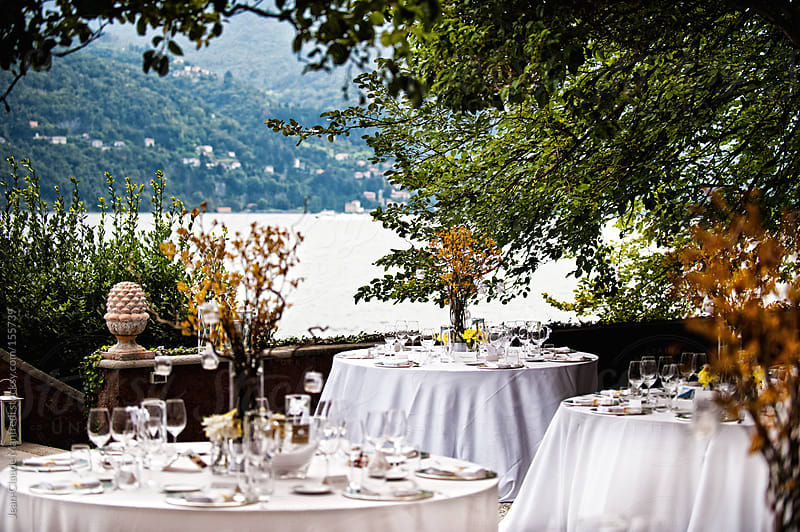 Table set for a wedding reception on the lake by Jean-Claude Manfredi for Stocksy United