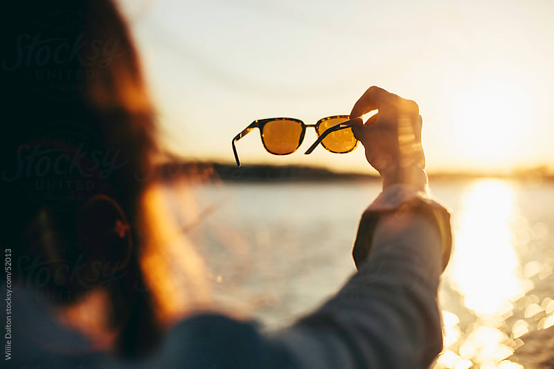 Woman Holds Sunglasses up to Setting Sun by Willie Dalton for Stocksy United