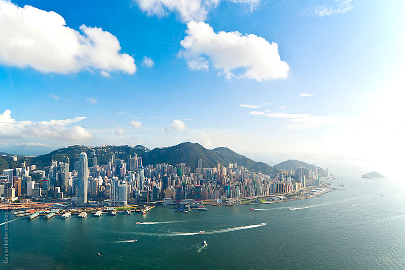 Elevated view across the busy Hong Kong harbour,  Central district of Hong Kong Island and Victoria  by Gavin Hellier for Stocksy United