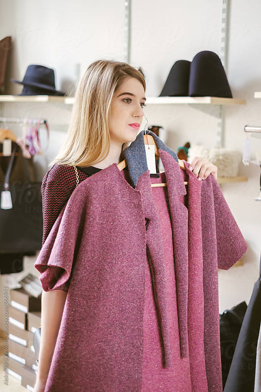 Blond Woman Looking at the Pink Coat in the Clothing Store by Aleksandra Jankovic for Stocksy United
