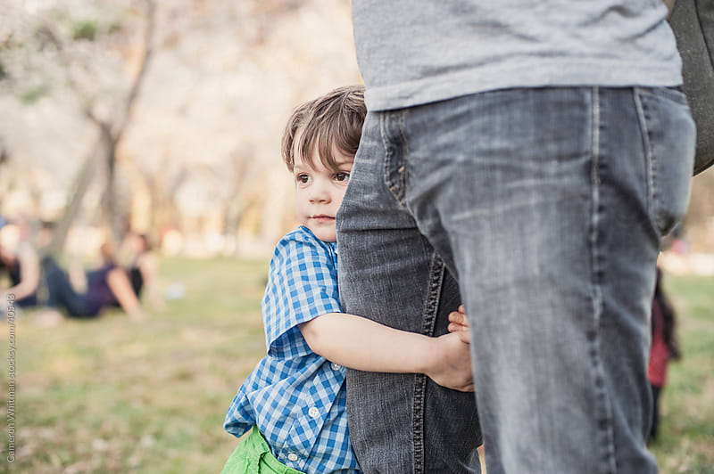 Little Boy Holding Onto His Father's Leg While At The Park by Cameron Whitman for Stocksy United