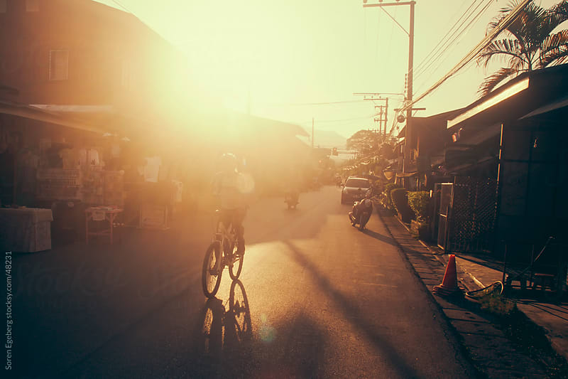 Man bicycling down the street in Pai Mae Hong Son with sun from the back by Soren Egeberg for Stocksy United