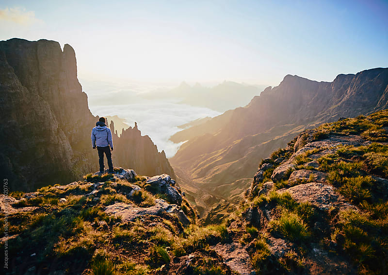 A Male hiker standing on a mountain edge admiring the spired mountain valley at sunrise. by Jacques van Zyl for Stocksy United