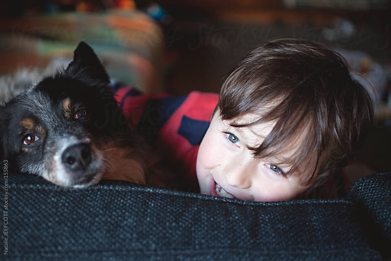 A young boy sits and cuddles his pet dog on a couch by Natalie JEFFCOTT for Stocksy United