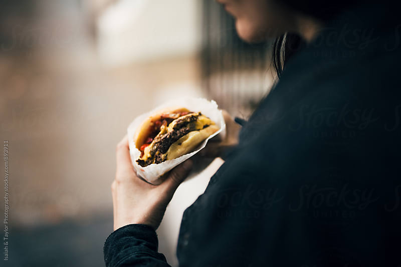 Woman eating a burger by Isaiah & Taylor Photography for Stocksy United