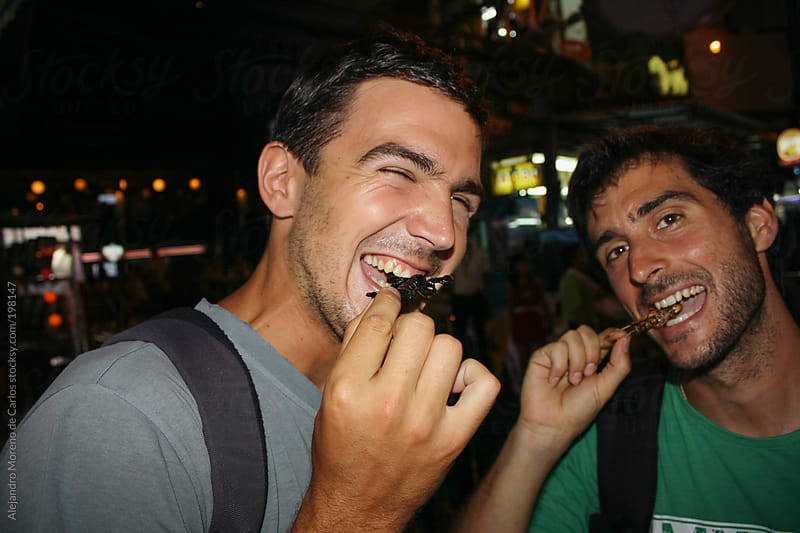 Two young friends tasting fried insects on Asia busy street by Alejandro Moreno de Carlos for Stocksy United