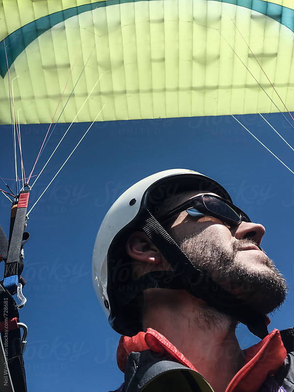 Close up of young man paragliding by Neil Warburton for Stocksy United