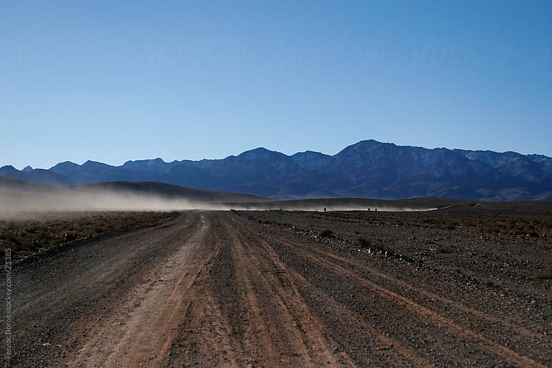 Dust trail behind Rally bikers in Morocco by Ferenc Boros for Stocksy United