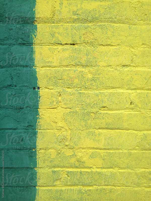 Urban background, green and yellow painted brick walls. by Shikhar Bhattarai for Stocksy United