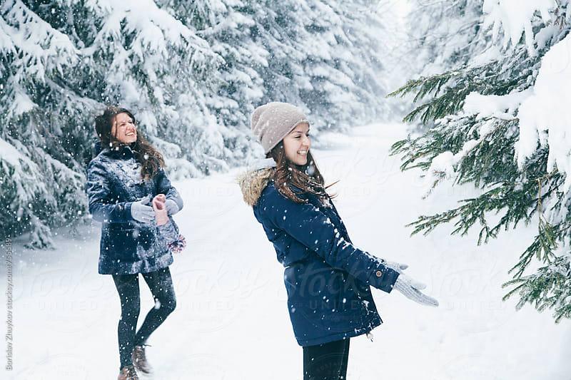 Two happy young female friends enjoying winter by Borislav Zhuykov for Stocksy United