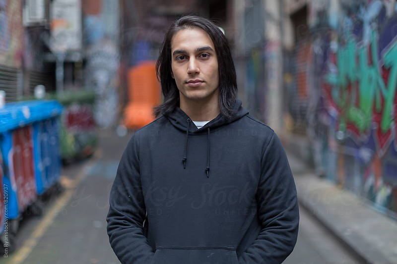 Young man with long hair in grungy alley looking to camera by Ben Ryan for Stocksy United