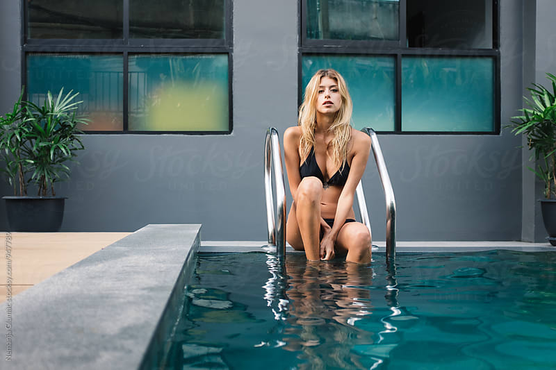 Attractive Blonde Woman Sitting By The Pool by Nemanja Glumac for Stocksy United